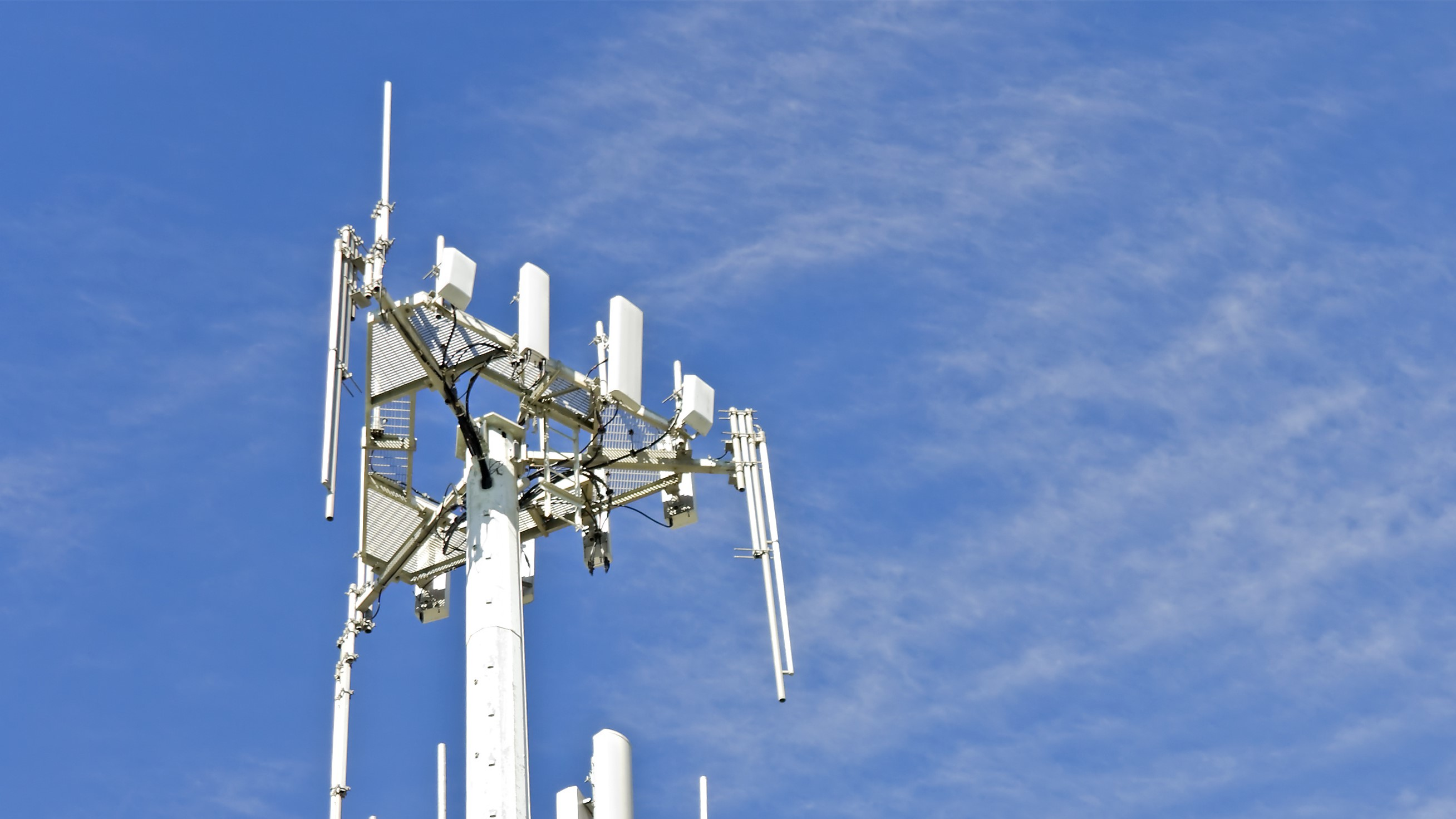 Cell phone telecommunication tower,blue sky,wispy clouds