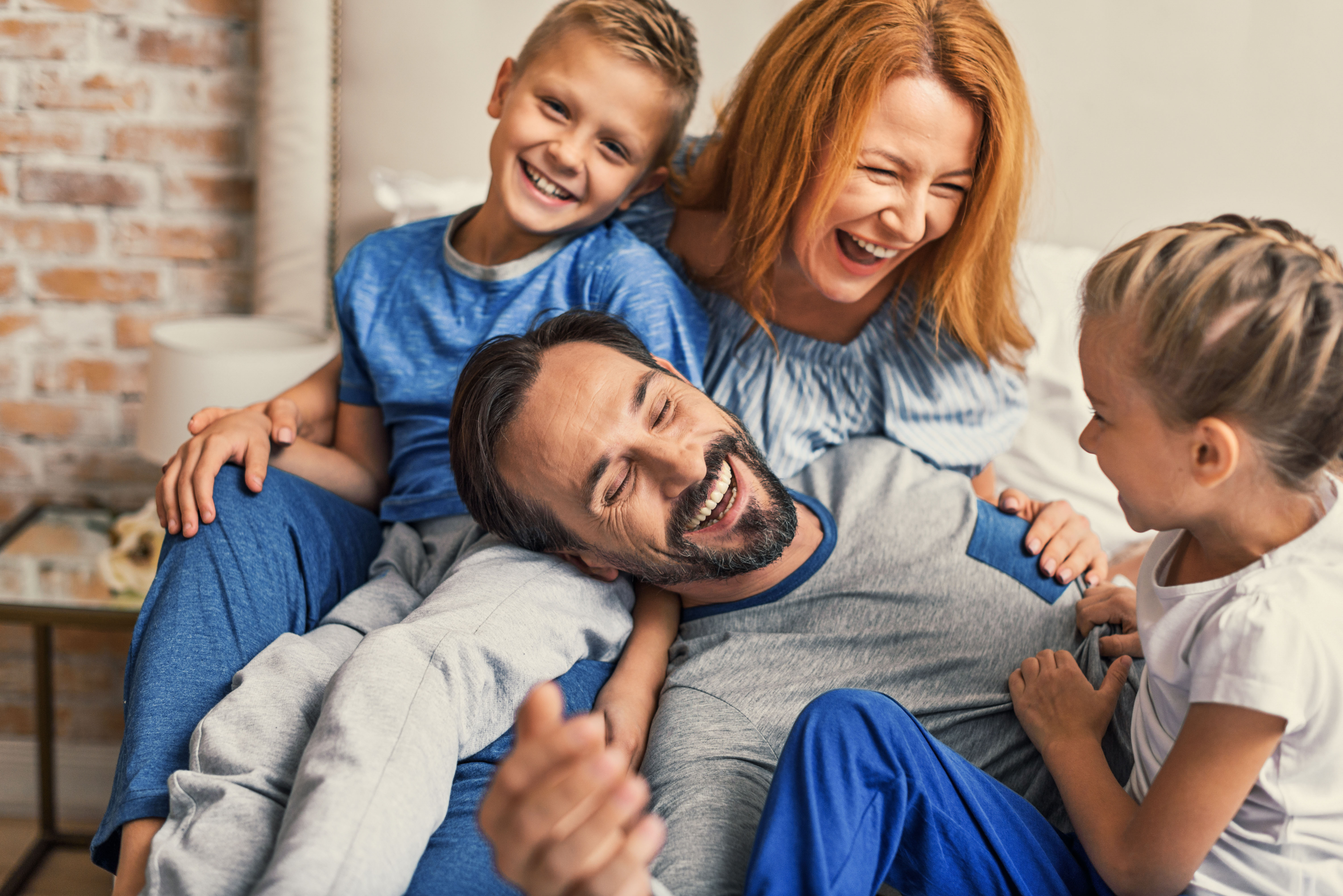 Happy family lying down on bed at home